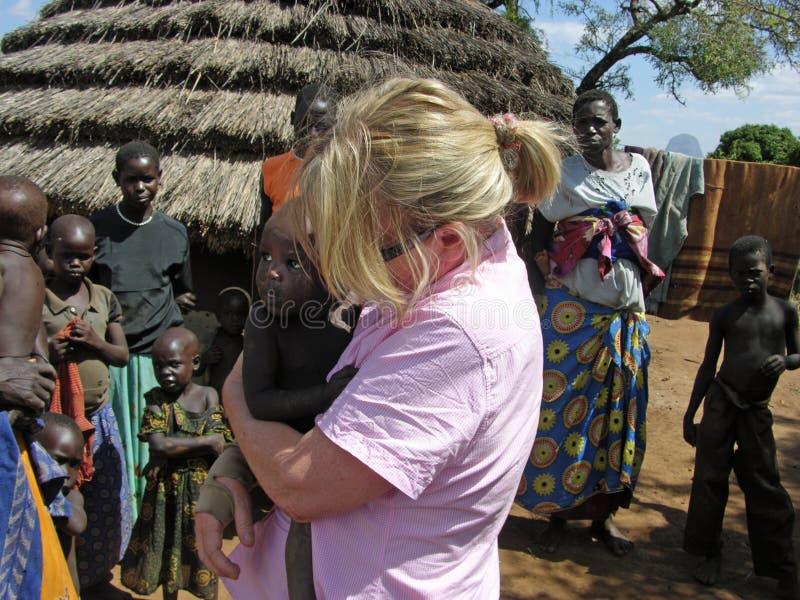 在村庄非洲帮助抱着饿的饥饿的非洲婴孩的救援者 免版税库存照片