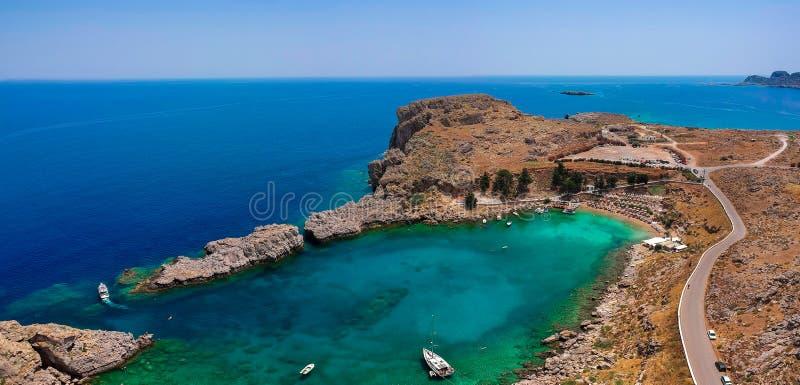 在村庄Lindos,罗得岛海岛,十二群岛,希腊附近的空中俯视图寄生虫照片圣保罗海湾 晴朗的全景与 免版税库存图片