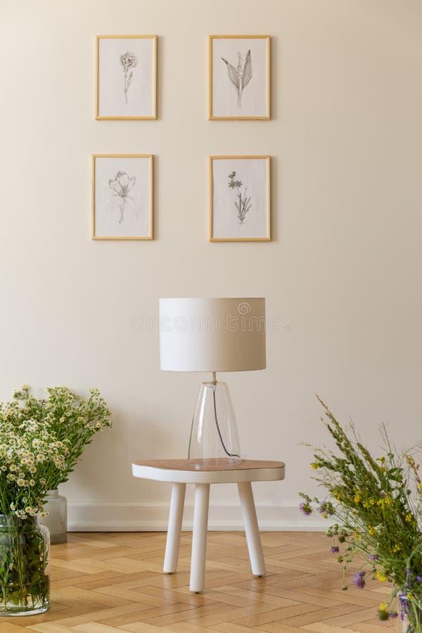 在束围拢的凳子的夜灯野花对有自然图画的香草墙壁在一间木地板屋子我 免版税库存照片
