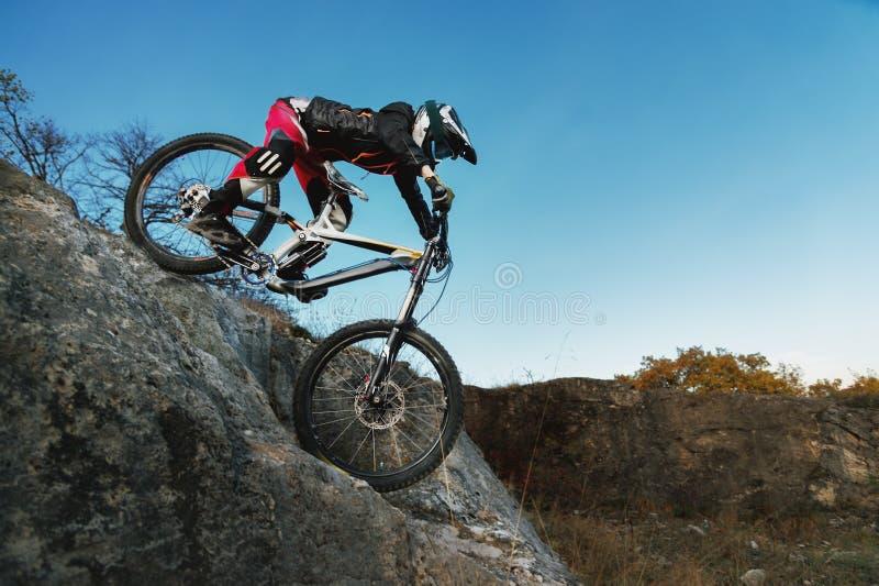 在来自下来峭壁的mtb自行车的年轻车手反对蓝天 免版税库存照片