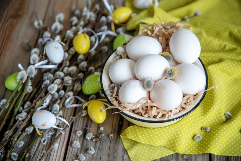 在杨柳分支的复活节彩蛋用在黄色板材的白鸡蛋在木桌上 库存图片