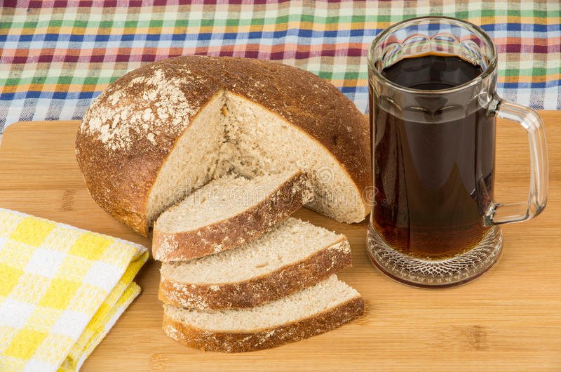 在杯子、餐巾和面包片的俄国kvas 图库摄影