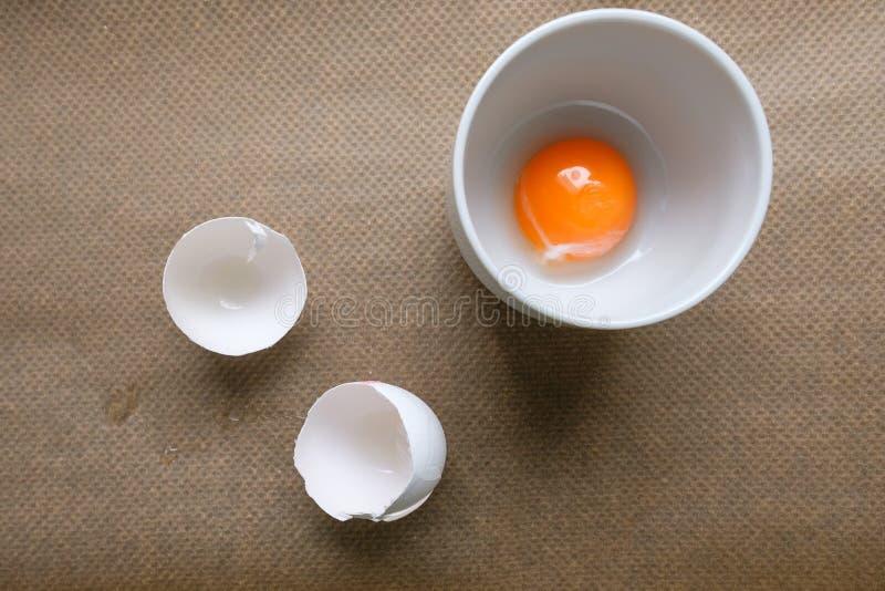 在杯子和白鸡蛋壳的蛋黄 免版税库存图片