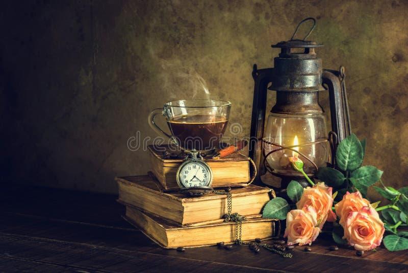 在杯子玻璃的咖啡在旧书和与煤油灯的时钟葡萄酒上油烧与在年迈的木地板上的焕发柔光的灯笼 免版税库存照片