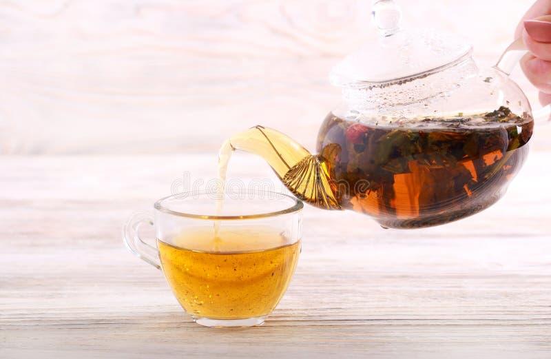 在杯子的倾吐的热的清凉茶 免版税库存图片