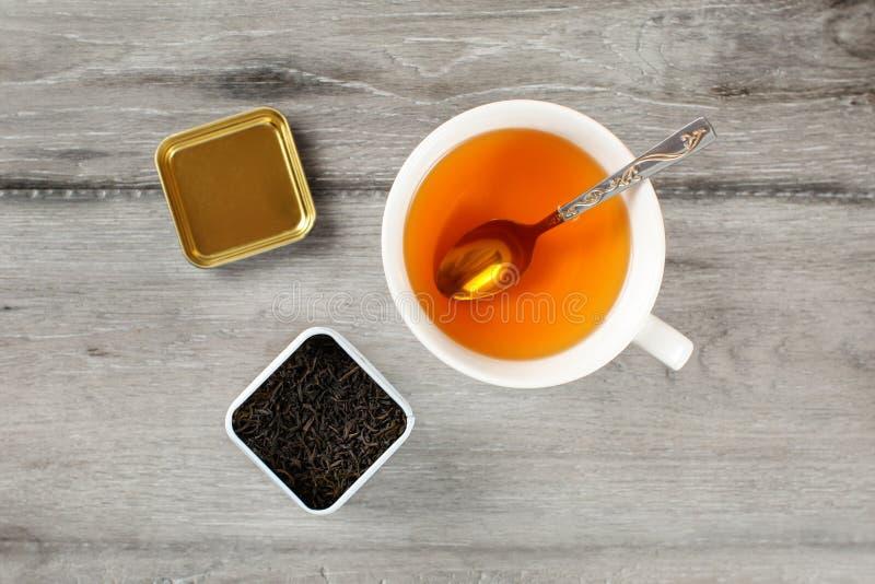 在杯子的台式视图与匙子和小型运车ful的热的琥珀色的茶 免版税库存照片