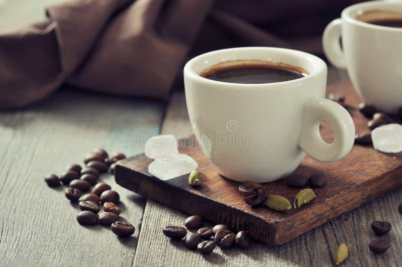 在杯子的咖啡用豆蔻果实 免版税库存图片