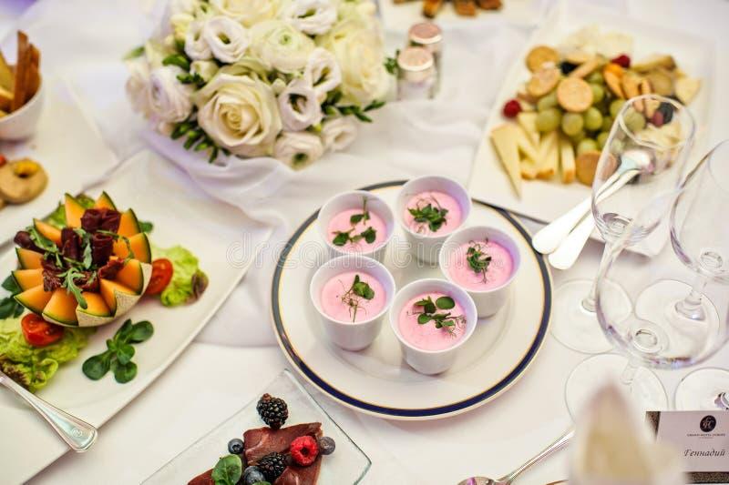 在杯子的桃红色帕纳陶砖 宴会桌在餐馆 图库摄影