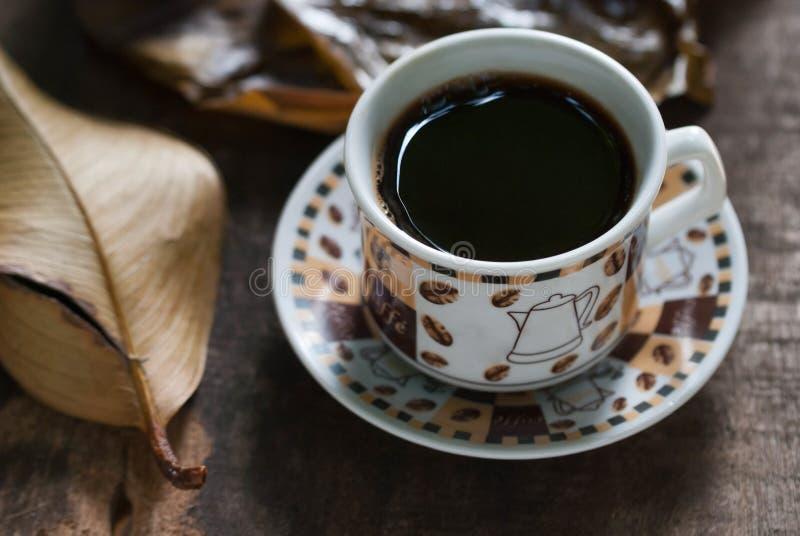 在杯子的热的咖啡在与叶子的老木桌上 免版税库存图片