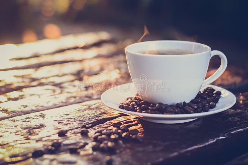 在杯子的热的咖啡在老木桌上用咖啡豆 免版税库存照片