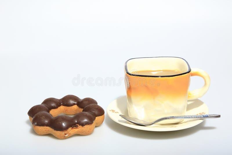 在杯子的热的咖啡有黑暗的巧克力油炸圈饼的,当食物背景 免版税图库摄影