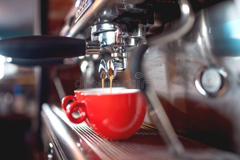 在杯子的煮浓咖啡器倾吐的咖啡在餐馆或客栈 与机械、堵塞器、咖啡和工具的Barista概念 免版税库存图片