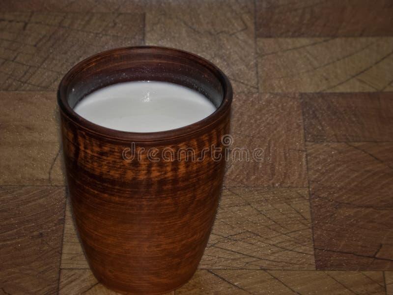 在杯子的牛奶由黏土制成在一张木桌 免版税库存照片