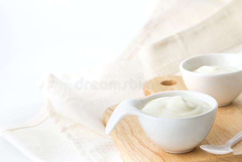 在杯子的自然乳白色酸奶在木板材 免版税库存图片