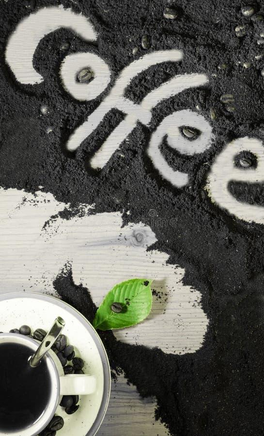 在杯子的顶视图与绿色叶子的热的无奶咖啡和文本措辞在被碾碎的咖啡纹理的英国`咖啡`写的手 免版税库存图片