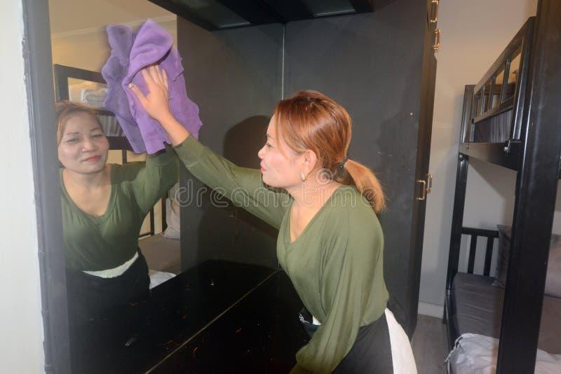 在杯的亚洲女性佣人或管家清洁梳妆台 免版税库存图片