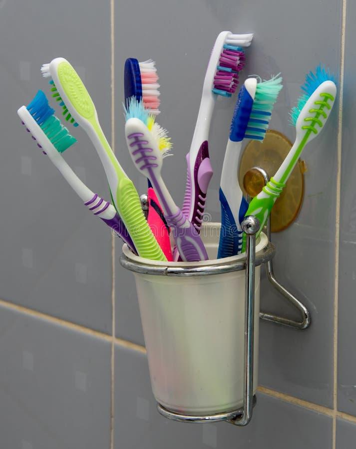 在杯的很大数量的牙刷附在墙壁在卫生间里 图库摄影