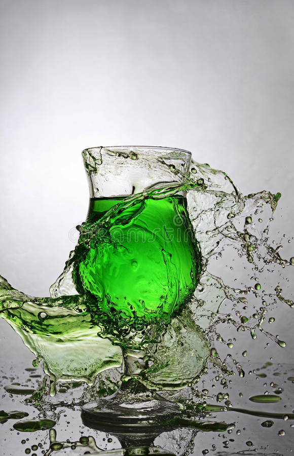 在杯的飞溅绿色酒精鸡尾酒饮料 图库摄影
