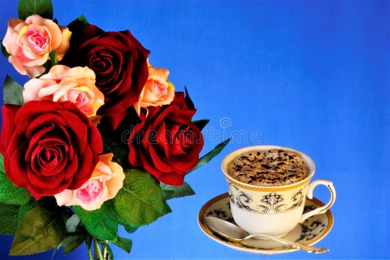 在杯自然鼓舞的可口饮料的咖啡和玫瑰花束一种快乐的心情的,在明亮的蓝色背景 库存照片