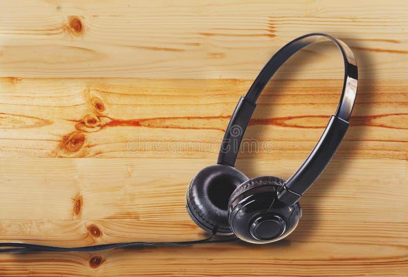 在松木地板或桌面桌上的耳机 免版税库存图片