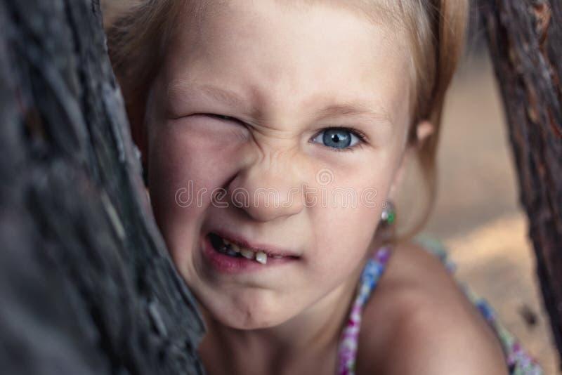 在松树附近的一女孩在她的嘴显示一个颤抖的乳齿 免版税库存照片