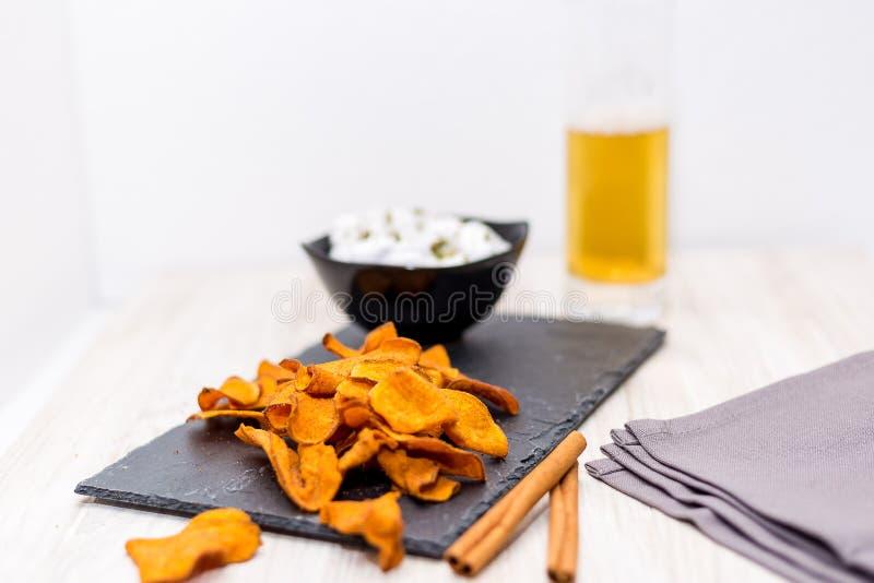 在板岩板啤酒调味汁孤立的油煎的地瓜在白色 图库摄影