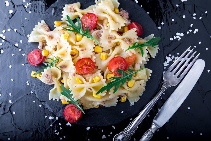 在板岩板材的意大利面制色拉用在刀子和匙子附近的蕃茄樱桃、金枪鱼、玉米和芝麻菜 顶视图 成份 烹调意大利语的食品成分 图库摄影