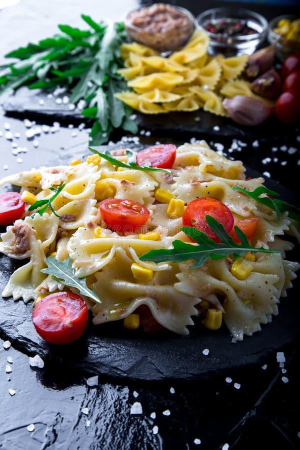 在板岩板材的意大利面制色拉用蕃茄樱桃、金枪鱼、玉米和芝麻菜 成份 烹调意大利语的食品成分 免版税库存图片