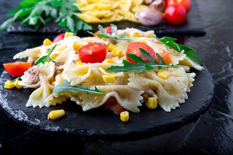 在板岩板材的意大利面制色拉用蕃茄樱桃、金枪鱼、玉米和芝麻菜 成份 烹调意大利语的食品成分 库存图片