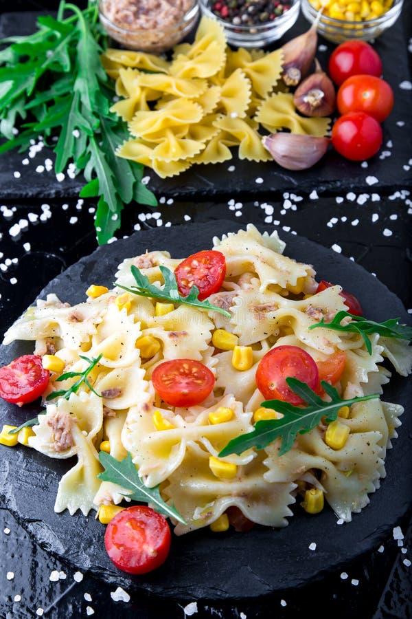 在板岩板材的意大利面制色拉用蕃茄樱桃、金枪鱼、玉米和芝麻菜 顶视图 成份 烹调意大利语的食品成分 库存照片