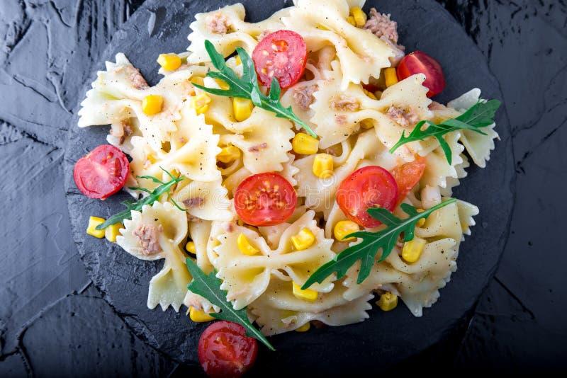 在板岩板材的意大利面制色拉用蕃茄樱桃、金枪鱼、玉米和芝麻菜 顶视图 成份 烹调意大利语的食品成分 免版税库存图片