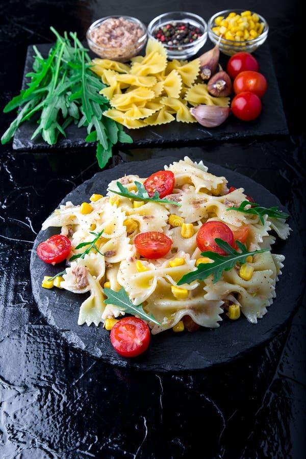 在板岩板材的意大利面制色拉用蕃茄樱桃、金枪鱼、玉米和芝麻菜 顶视图 成份 烹调意大利语的食品成分 库存图片
