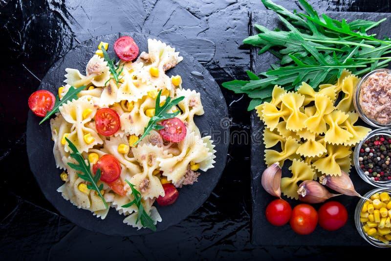 在板岩板材的意大利面制色拉用蕃茄樱桃、金枪鱼、玉米和芝麻菜 顶视图 成份 烹调意大利语的食品成分 图库摄影