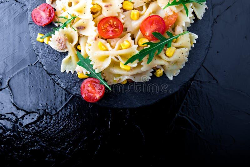在板岩板材的意大利面制色拉用蕃茄樱桃、金枪鱼、玉米和芝麻菜 顶视图 烹调意大利语的食品成分 复制空间 库存照片