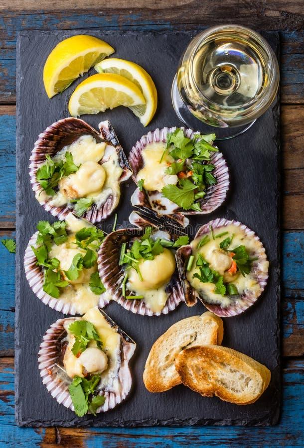 在板岩的被烘烤的扇贝用柠檬,香菜,在白葡萄酒上添面包 库存照片