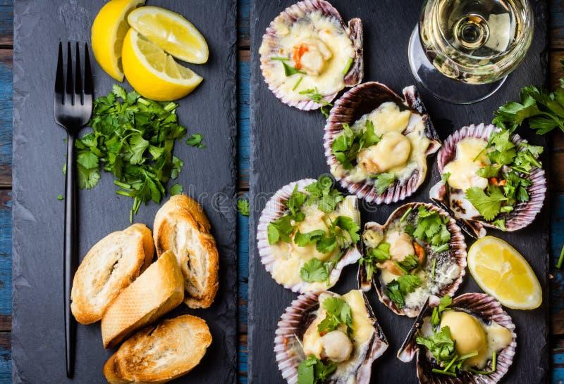 在板岩的被烘烤的扇贝用柠檬,香菜,在白葡萄酒上添面包 免版税库存照片