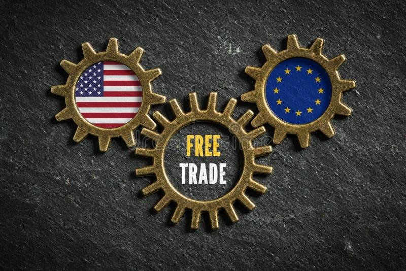 在板岩背景与美国和欧盟旗子和词`自由贸易`的三个钝齿轮在中部 库存图片