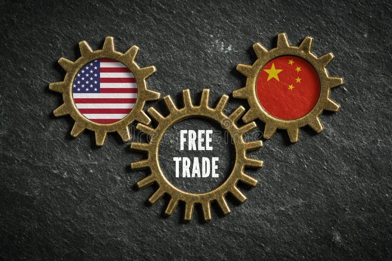 在板岩背景的三个钝齿轮与美国和中国的旗子和词'自由贸易' 免版税库存图片