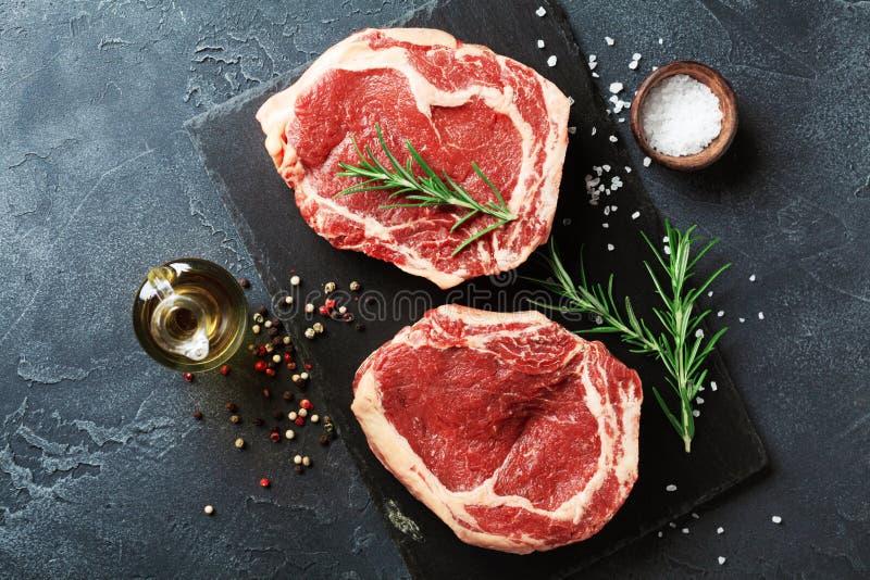 在板岩黑色委员会顶视图的新鲜的肉 未加工的牛排和香料烹调的 免版税图库摄影