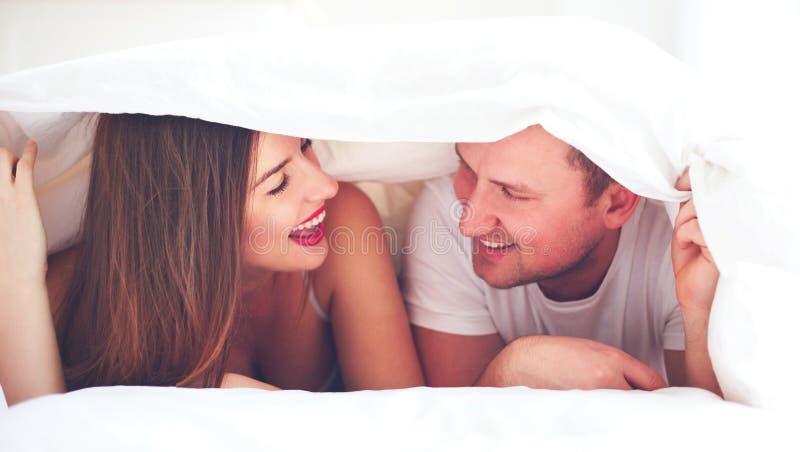 在板料下的愉快的夫妇,亲热 免版税库存照片