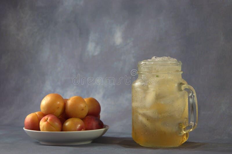 在板材和一个杯子的一些个新鲜的杏子与冰的杏子汁 r 图库摄影