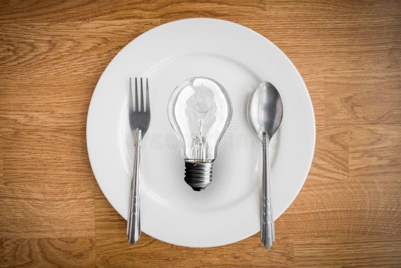 在板材和叉子的在木桌上的电灯泡和匙子 图库摄影