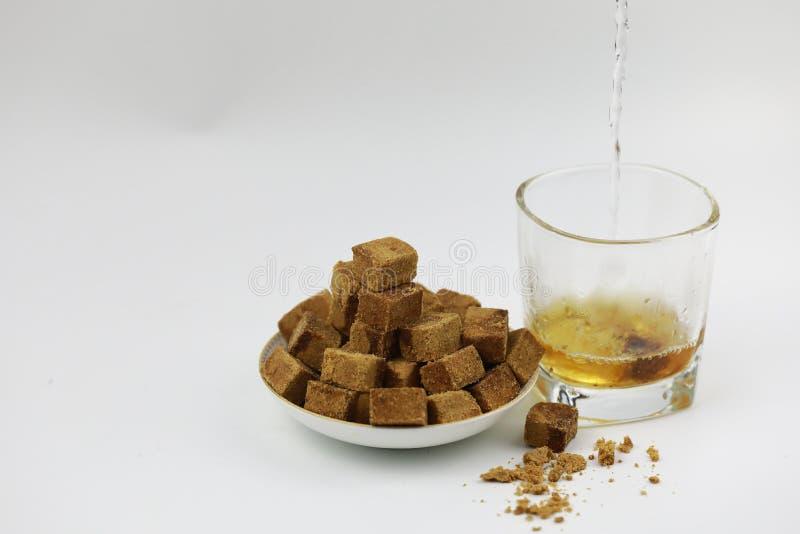 在板材和玻璃杯子的糖立方体用水 免版税图库摄影