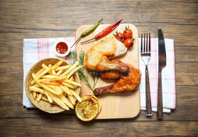 在板材木板的烤鸡腿用薯条篮子番茄酱蕃茄辣柠檬的辣椒 免版税库存图片