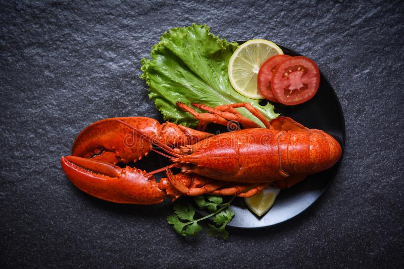 在板材海鲜的龙虾与柠檬沙拉莴苣菜和蕃茄在黑暗的背景 免版税库存照片
