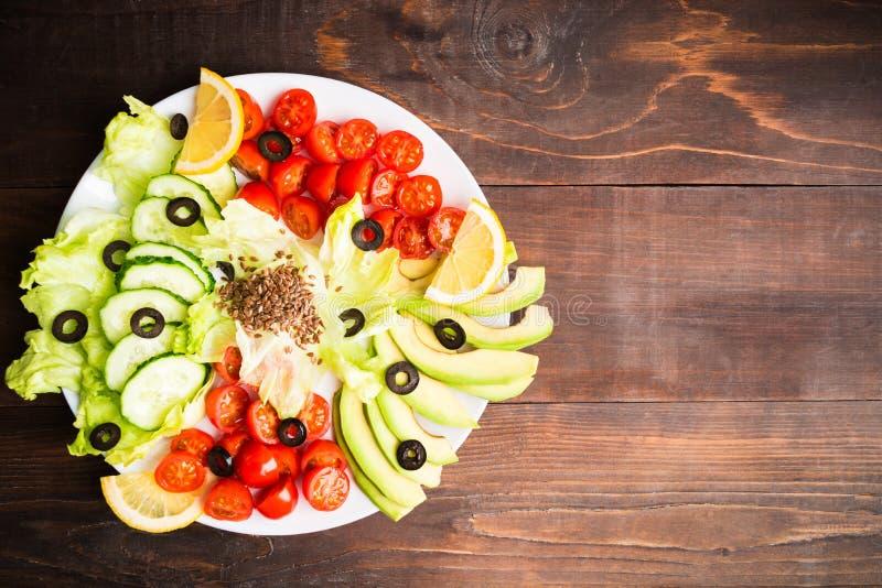 在板材用蕃茄,黄瓜,莴苣,鲕梨的沙拉柜台和 免版税库存照片