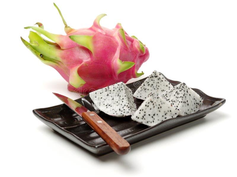 在板材的切成小方块的龙果子片对整个果子 图库摄影