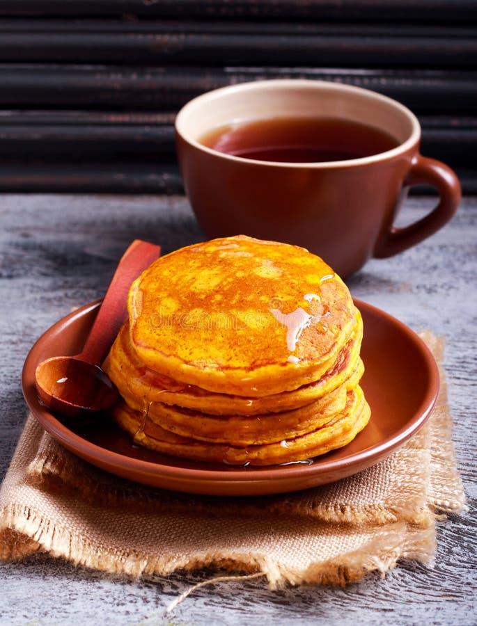 在板材的南瓜薄煎饼用蜂蜜 免版税库存图片