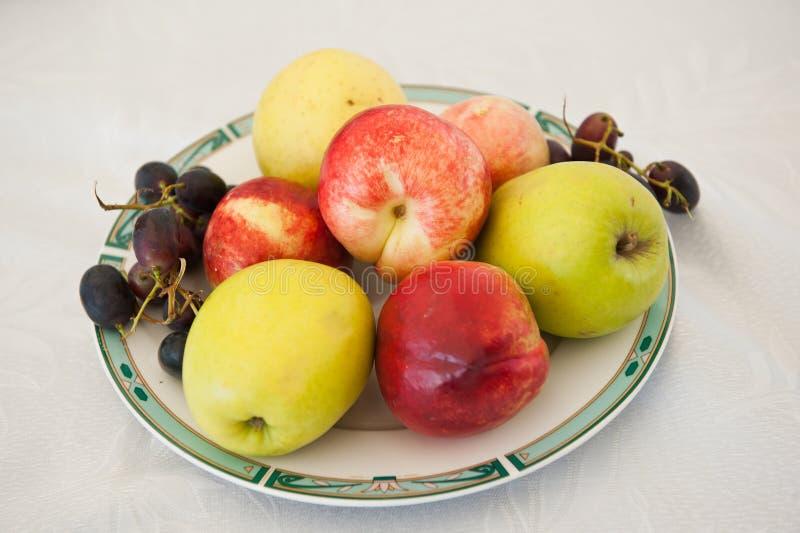 在板材的各种各样的果子 新鲜和色的苹果、葡萄和油桃在桌上 库存照片