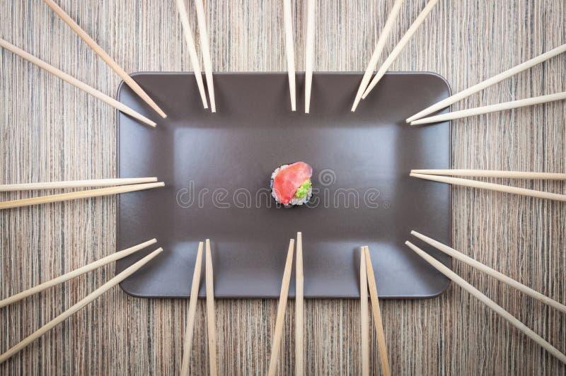 在板材的唯一寿司卷有许多的在木桌上的筷子 库存图片
